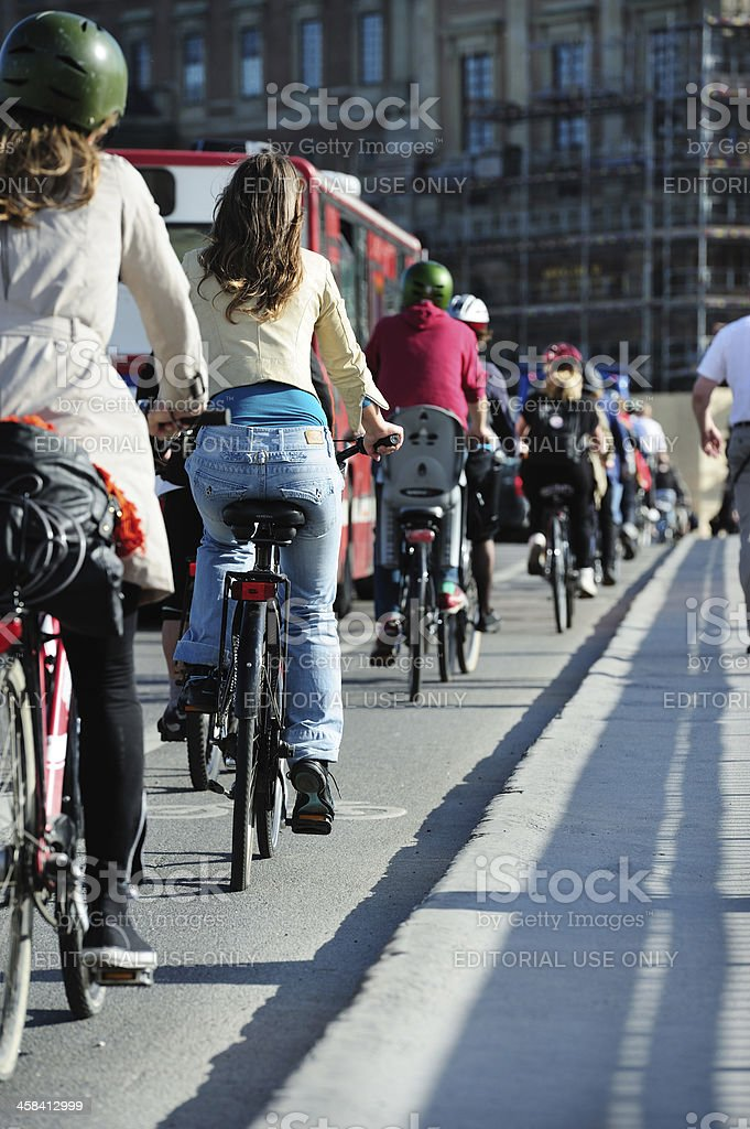 Young adults on bikes in traffic royalty-free stock photo