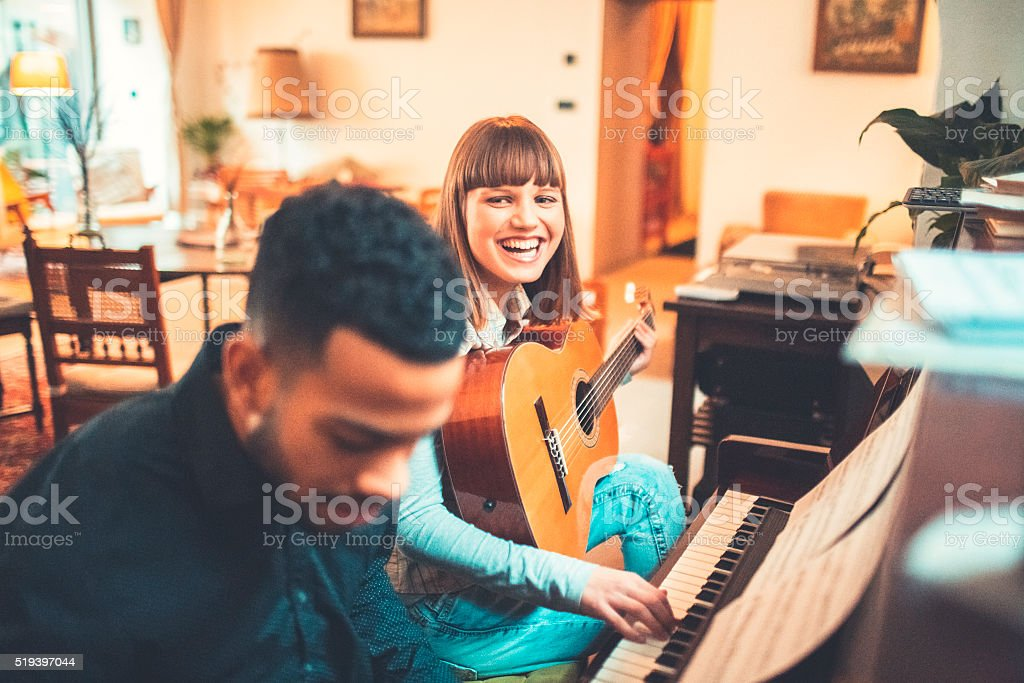 Young adults playing piano together stock photo