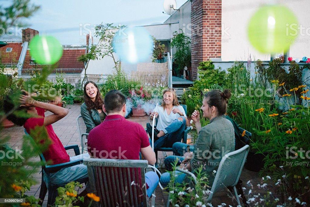 young adults, roof garden, talking, smoking Hookah stock photo