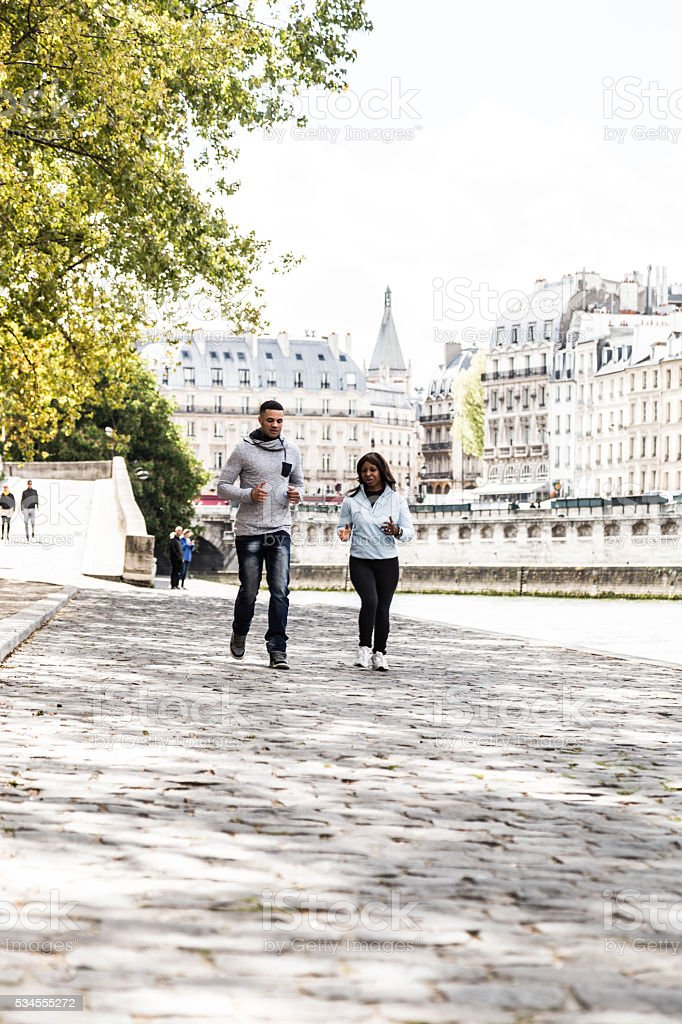 young adults running in park, Paris, France stock photo
