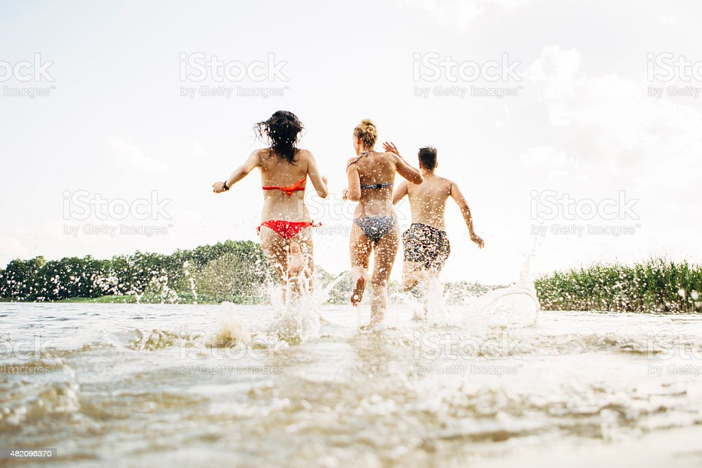 young adults running into lake, water splashes stock photo