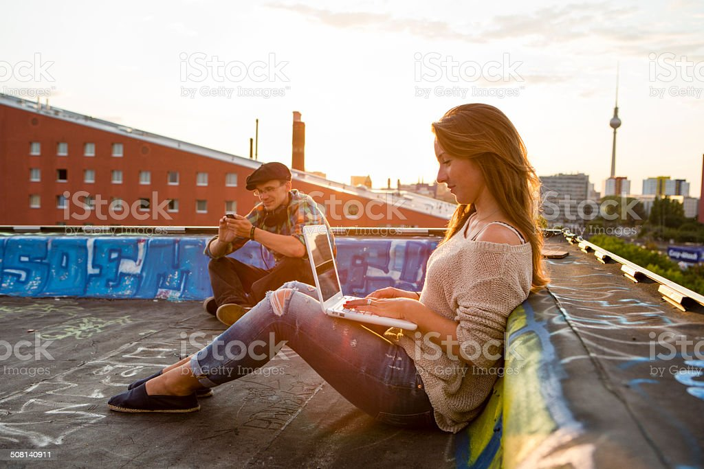young adults sitting on a roof, back lit stock photo