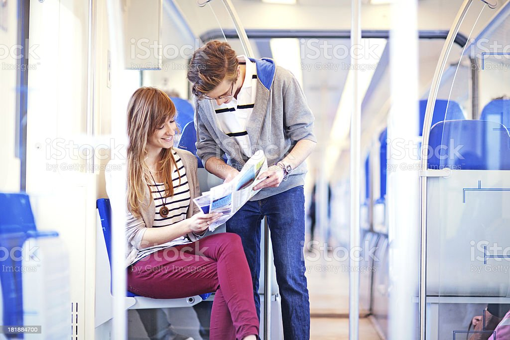 young adults traveling by train, looking at map royalty-free stock photo