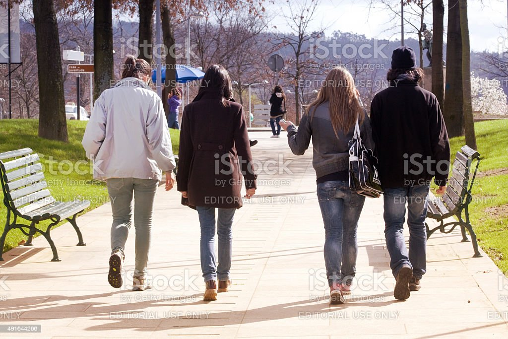 Young adults walking on a garden promenade. stock photo