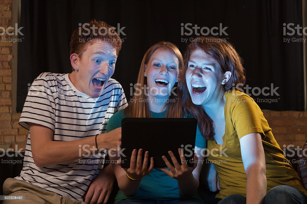 Young Adults Watching Movie on Tablet Computer, Friends Laughing Together stock photo