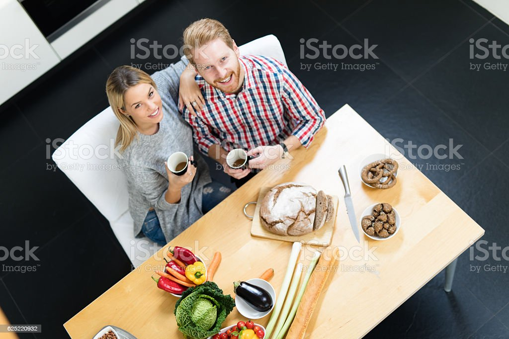 Young affectionate couple spending time in the kitchen flirting stock photo