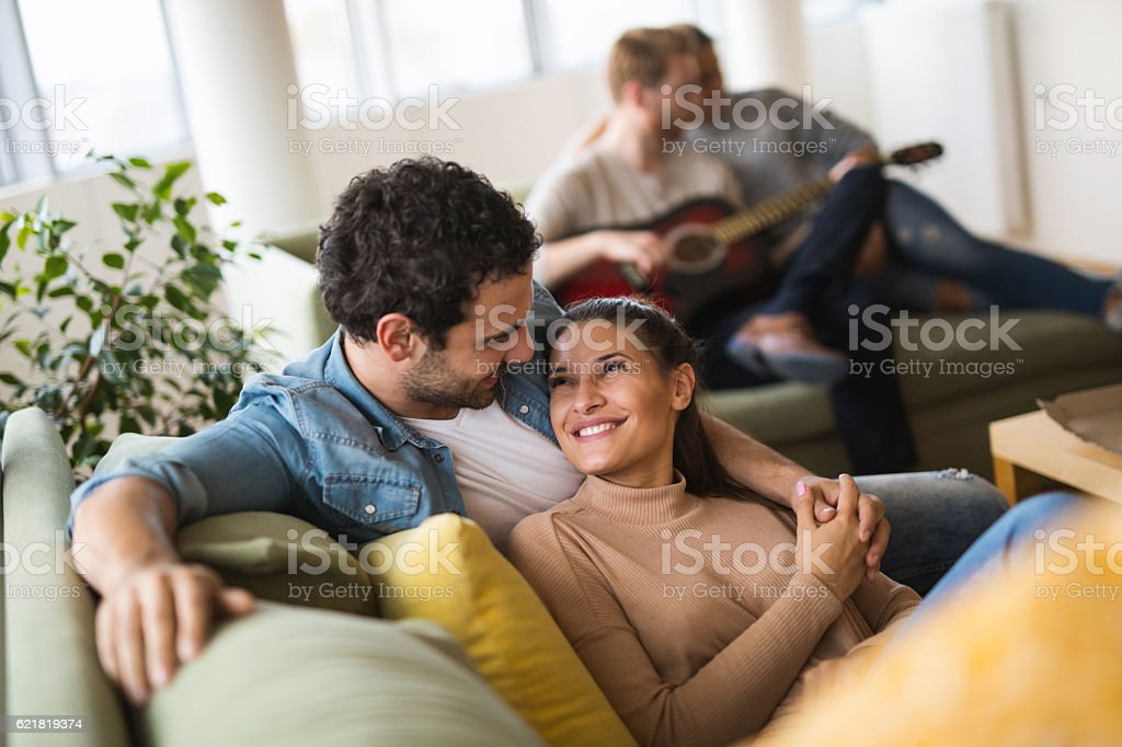 Young affectionate heterosexual couple resting on sofa and flirting stock photo