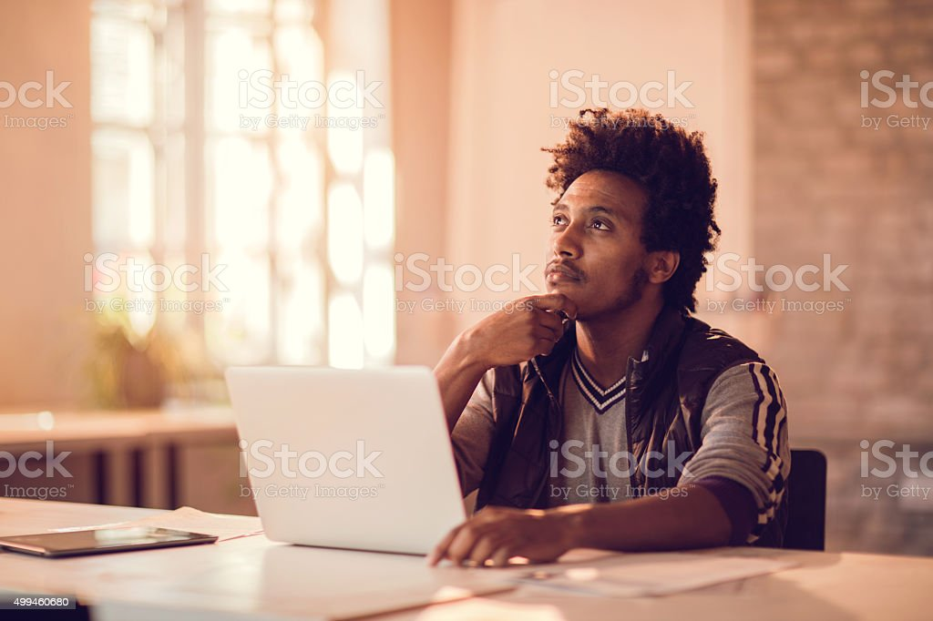 Young African American businessman thinking of new business idea. stock photo