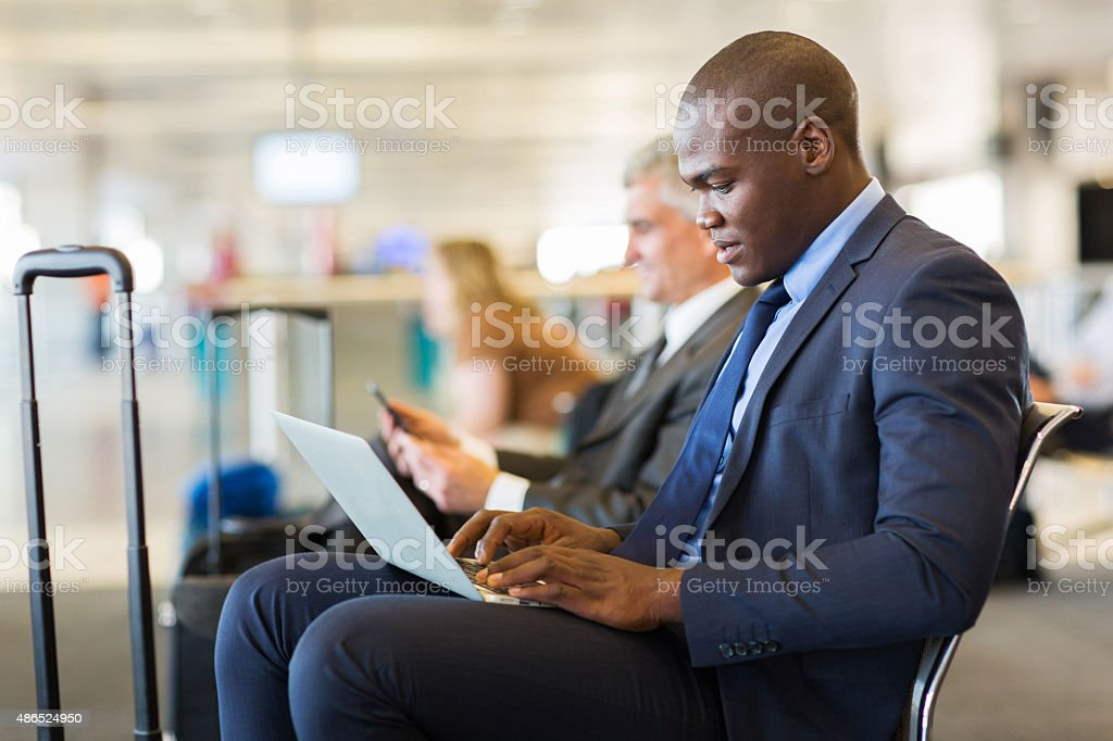 young african american businessman waiting for his flight stock photo