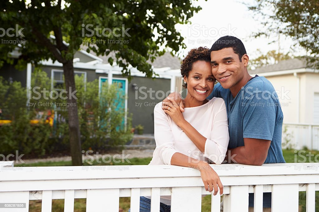 Young African American couple embrace outside their house stock photo