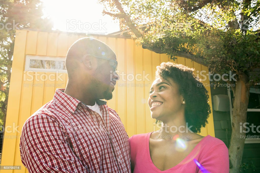 Young African American couple face to face in garden, smiling stock photo