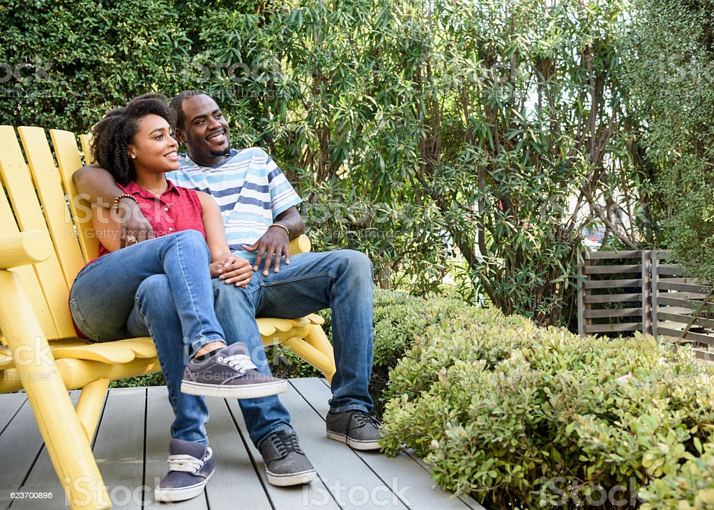 Young african American couple looking away on garden bench stock photo