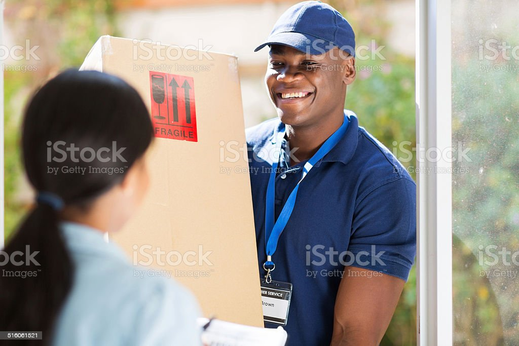 young african american delivery man delivering a package stock photo