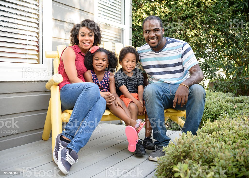 Young African American family sitting on bench outside house stock photo