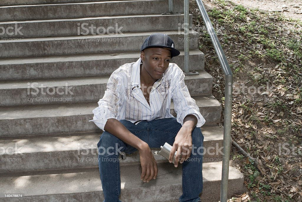 Young African American Guy Sitting in Park Holding Flask royalty-free stock photo