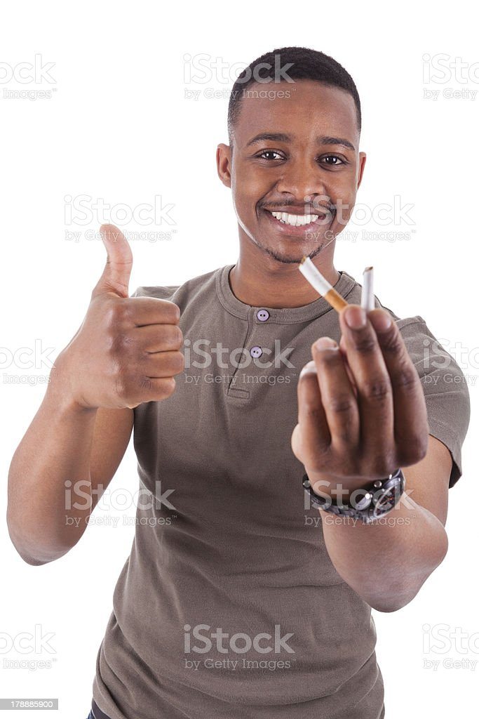 Young african american man showing  a broken  cigarette stock photo