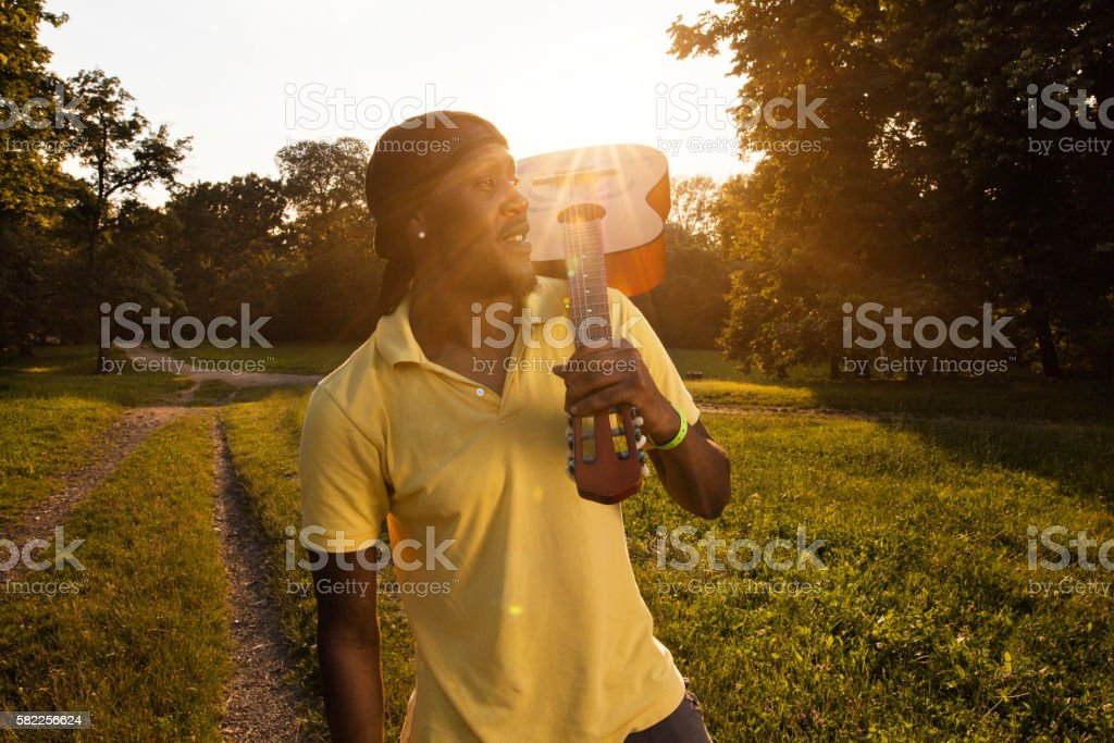 Young African American man walking in park with acoustic guitar. stock photo