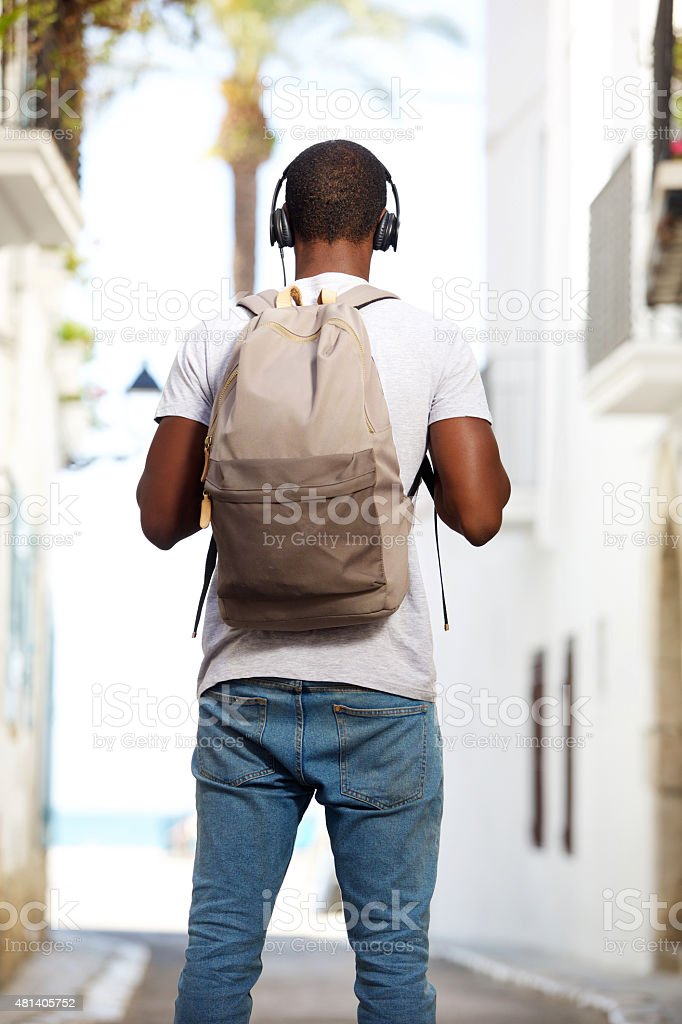 Young african american man with bag standing in street stock photo