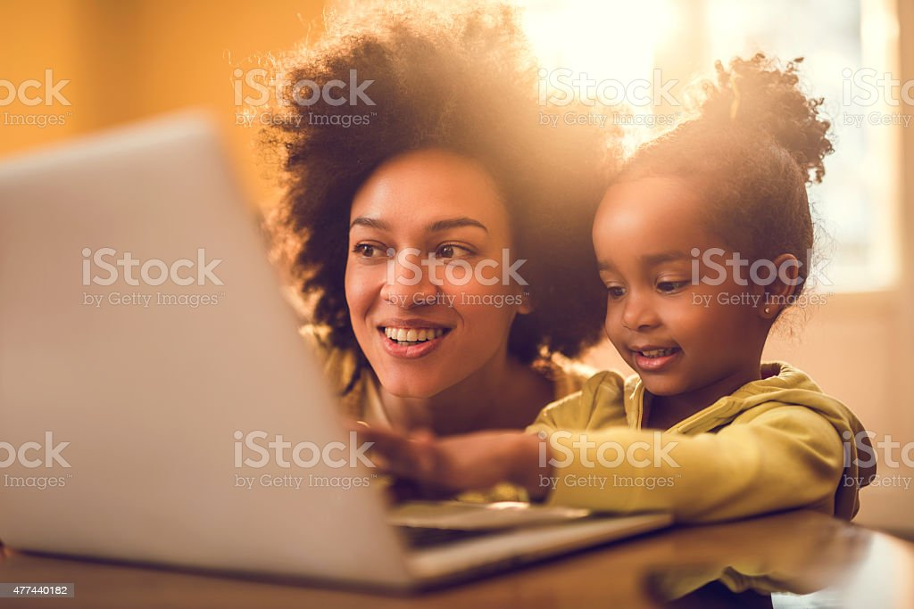 Young African American mother and her little girl using computer. stock photo