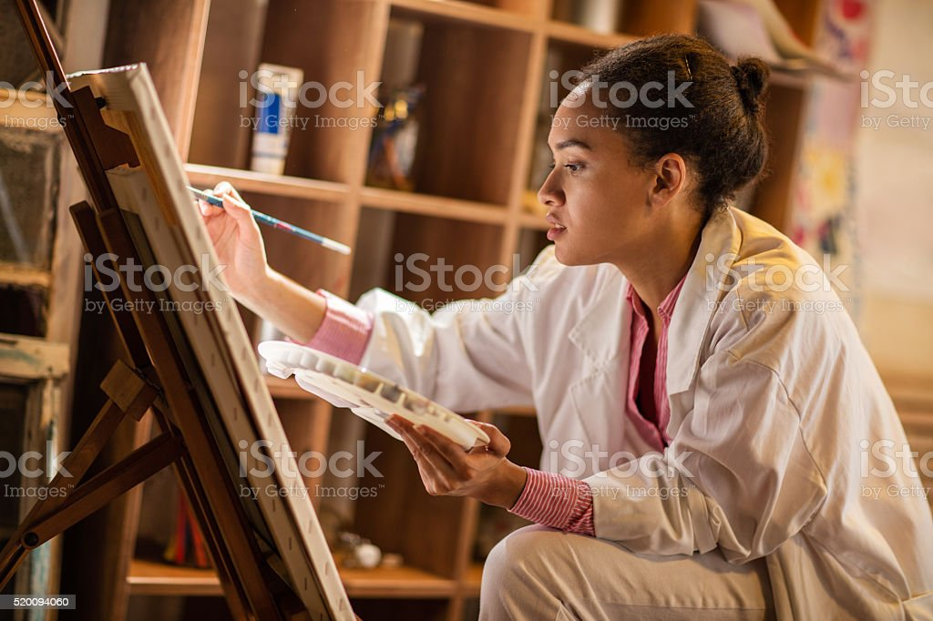 Young African American painter working in her studio. stock photo