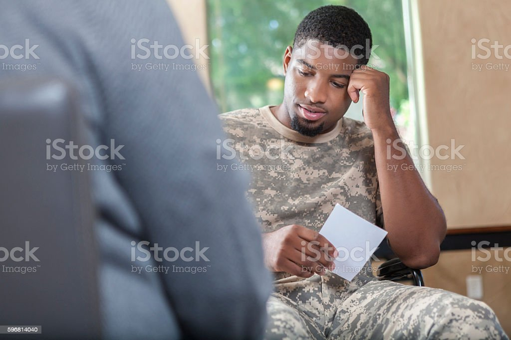 Young African American soldier talking to counselor about prescription stock photo