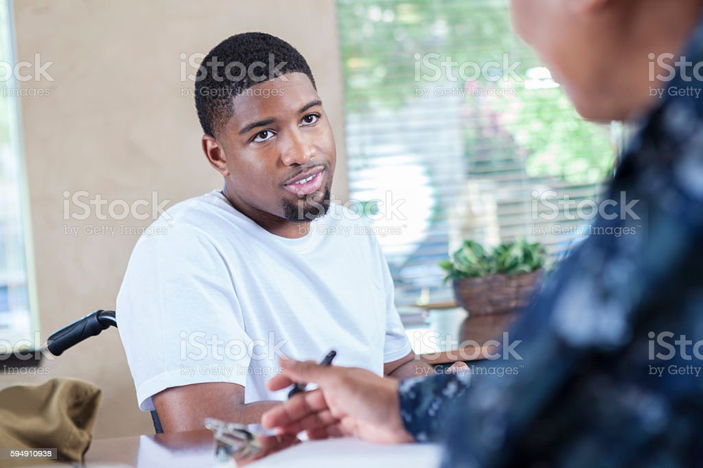Young African American soldier talking to veteran's counselor stock photo