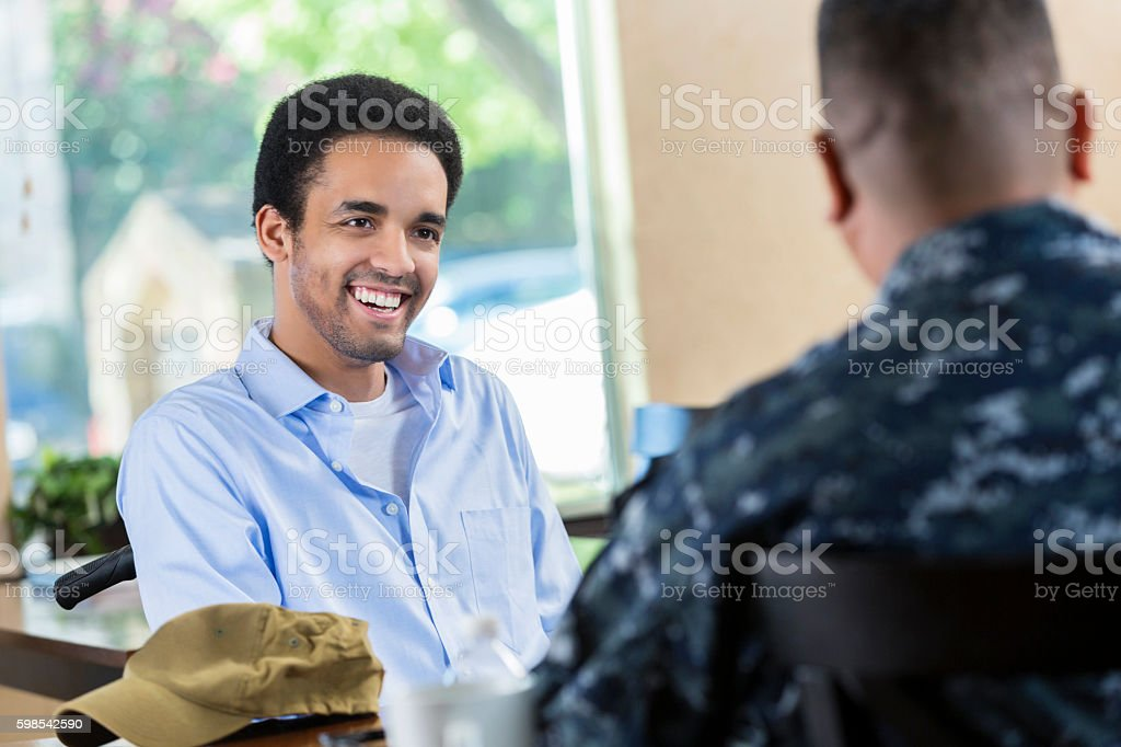 Young African American veteran talking to military counselor stock photo