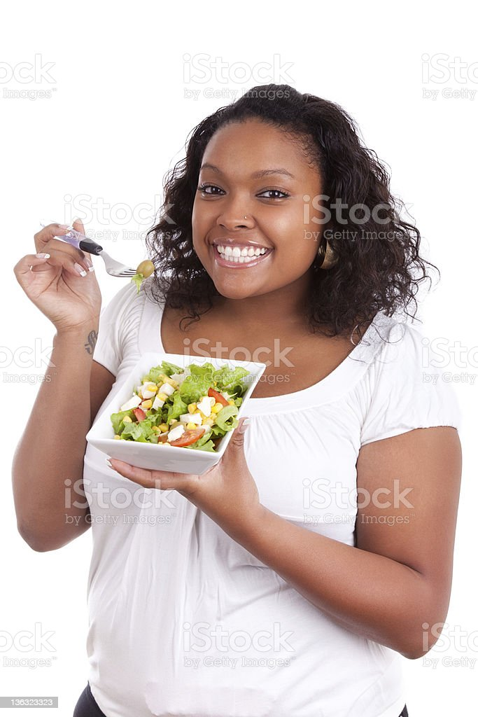 Young african american woman eating salad stock photo