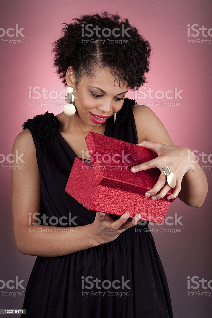 Young African American woman opening a gift royalty-free stock photo