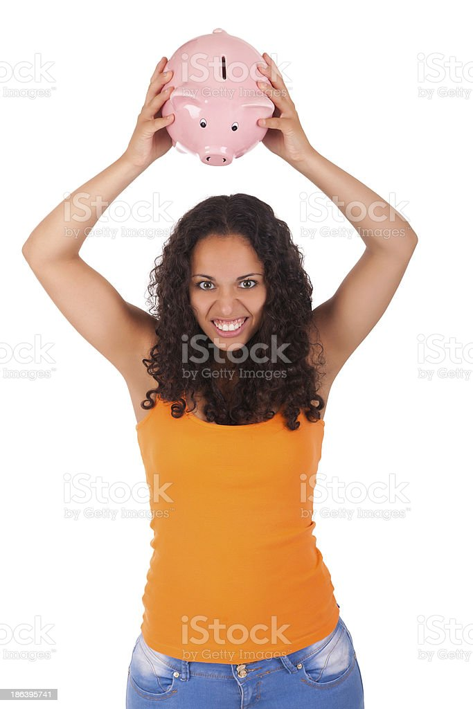 Young african american woman putting coin in piggy bank royalty-free stock photo