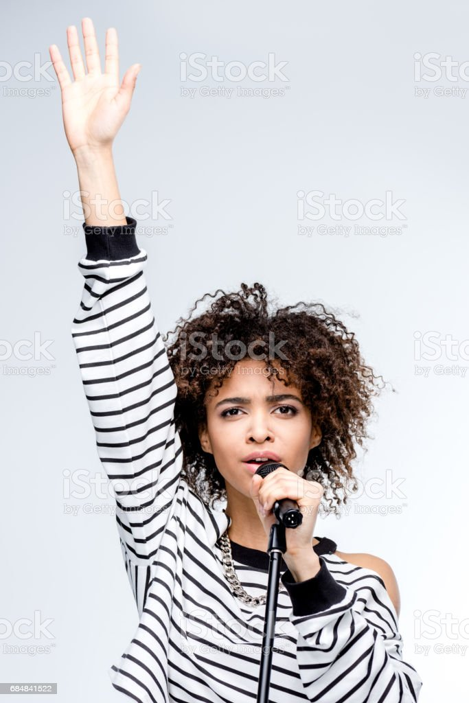 young african american woman singing with microphone isolated on grey, female singer with microphone concept stock photo