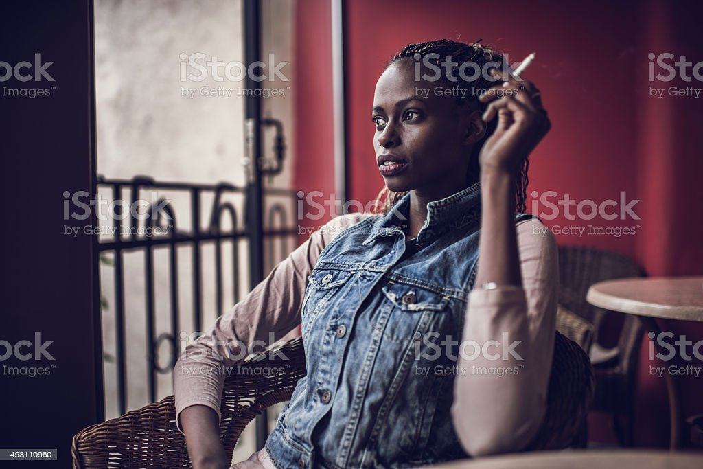 Young African American woman smoking a cigarette on a terrace. stock photo