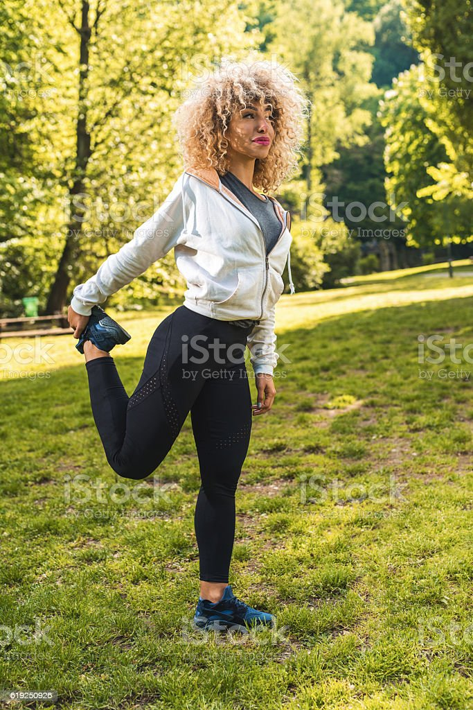 Young African American woman stretching her leg in nature. stock photo
