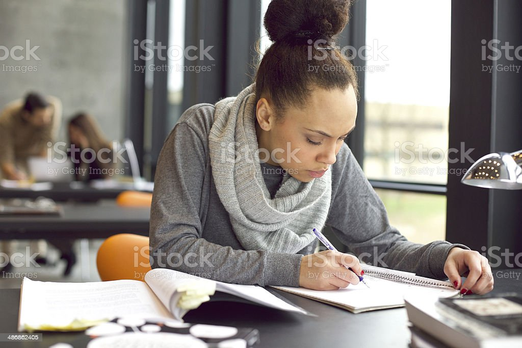 Young african american woman taking notes for her study stock photo