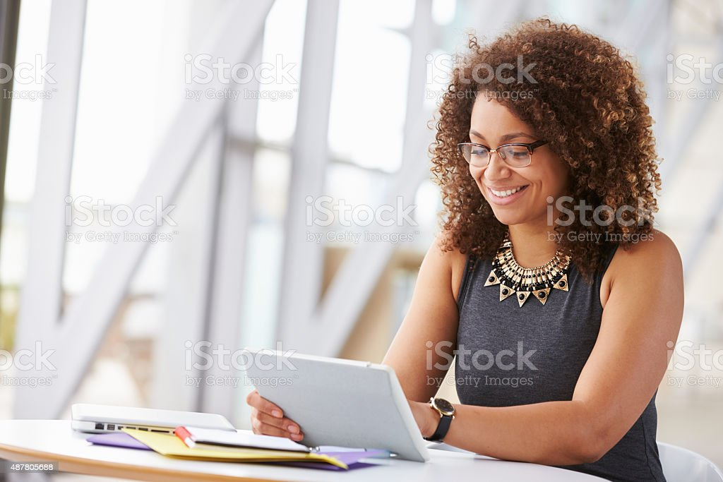 Young African American woman working with tablet in office stock photo