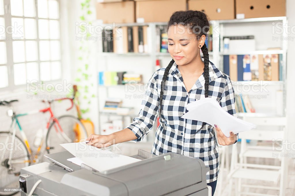Young african assistant using copy machine at workplace stock photo