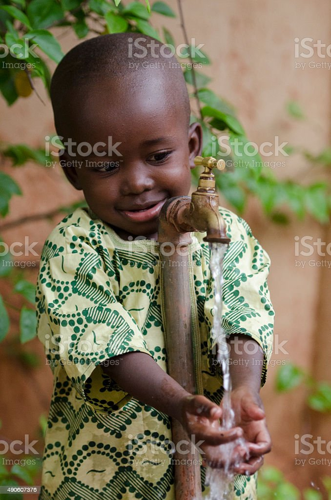 Young African Boy Asking for Clean Water from Tap stock photo