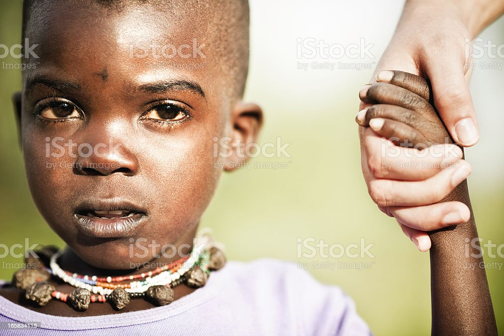 Young African Boy Receiving a Helping Hand stock photo