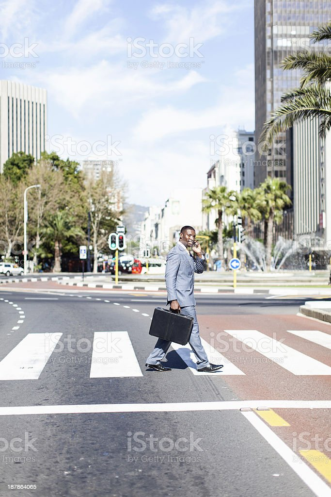 Young african businessman crossing the road. royalty-free stock photo
