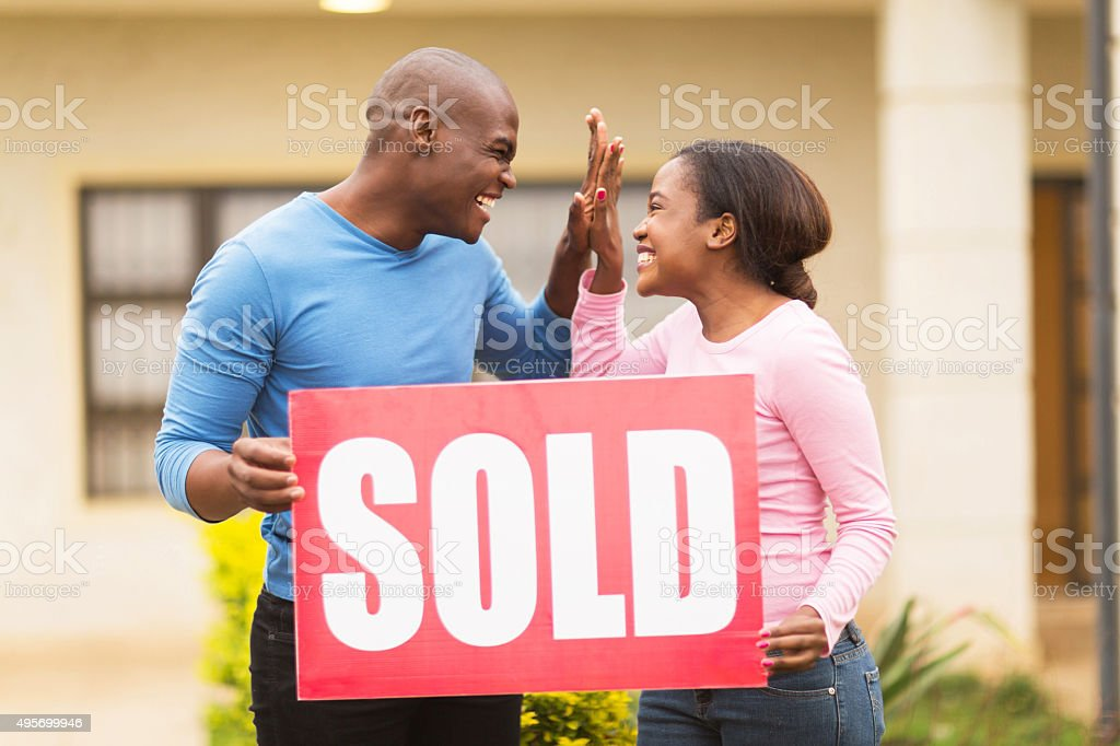 young african couple celebrating their house been sold stock photo