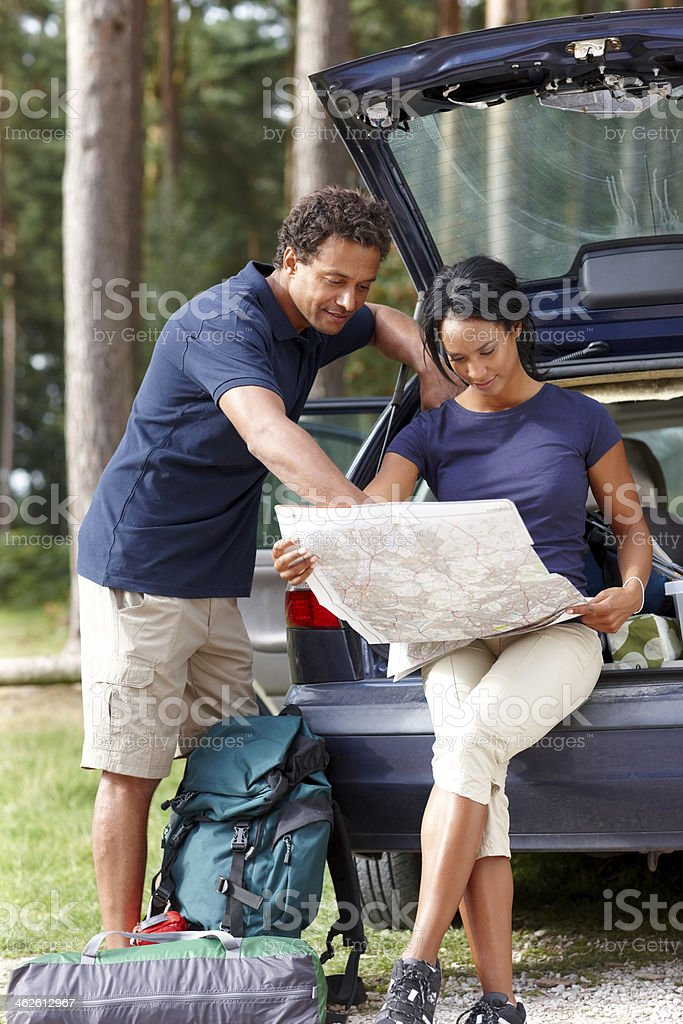 Young african couple looking a place for camping on map royalty-free stock photo