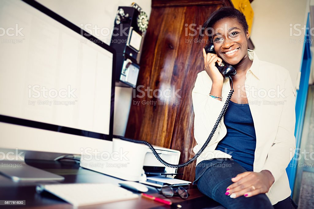 Young African European woman on the phone in studio stock photo