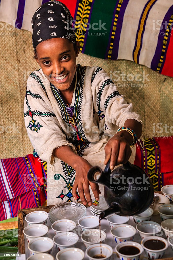 Young African girl preparing coffee, Ethiopia. East Africa stock photo