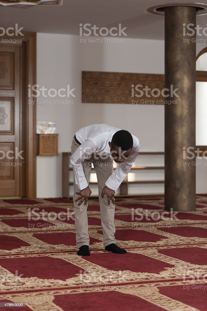 Young African Guy Praying In Mosque stock photo