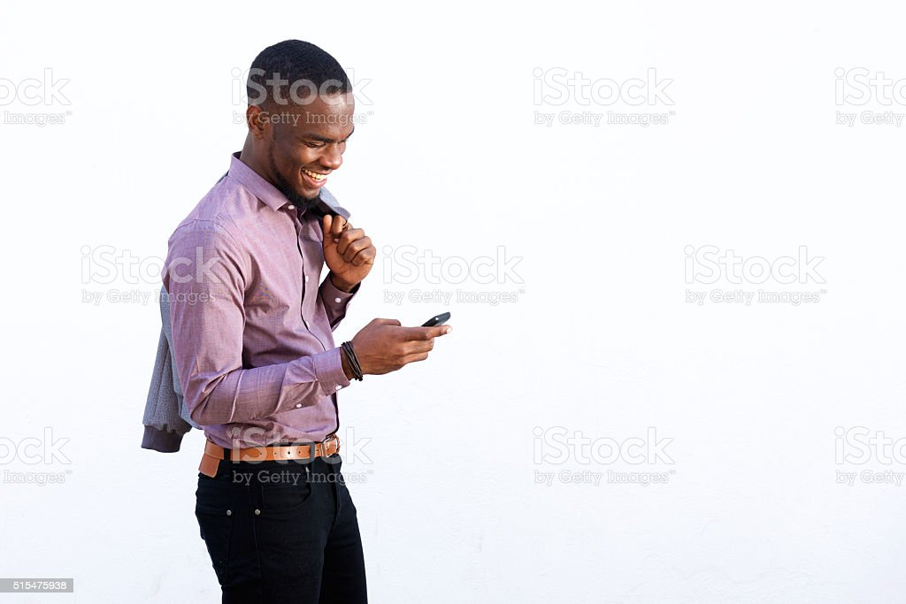 Young african guy reading text message on cell phone stock photo