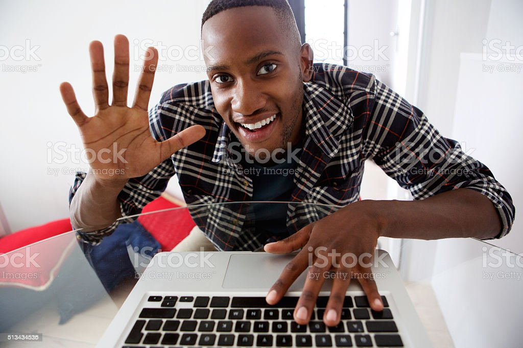 Young african guy video chatting on laptop at home stock photo