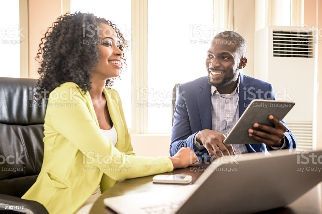 Young African man and woman in office with tablet stock photo