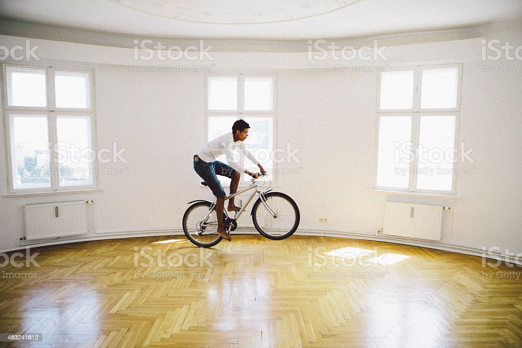 young african man drive his bicycle in unfurnished loft apartment stock photo