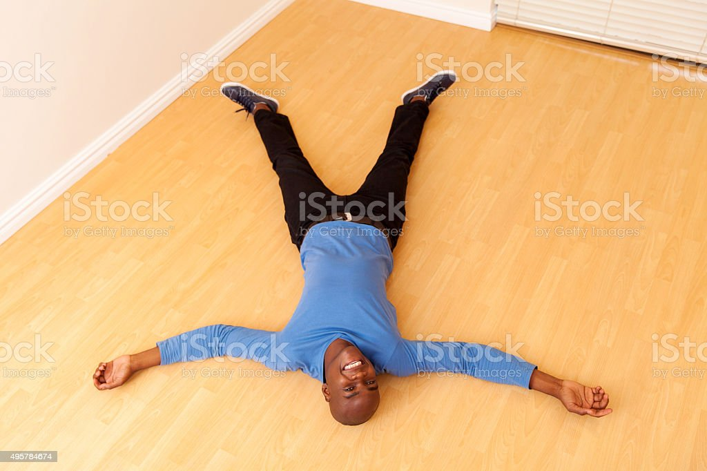 young african man lying on the floor stock photo