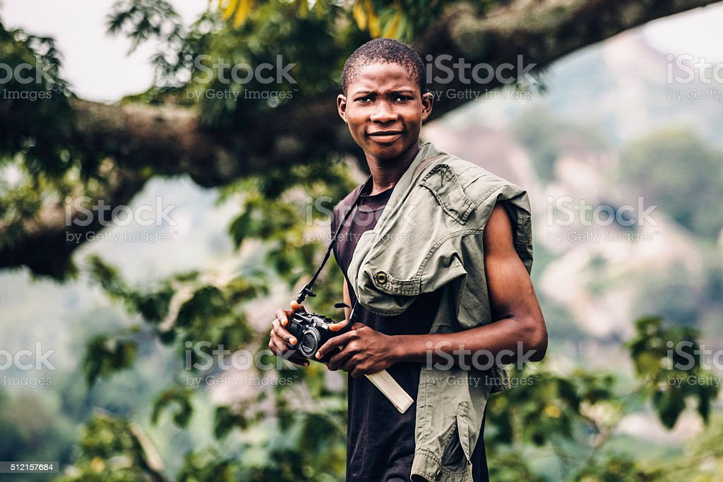 Young african man outdoors with camera. stock photo